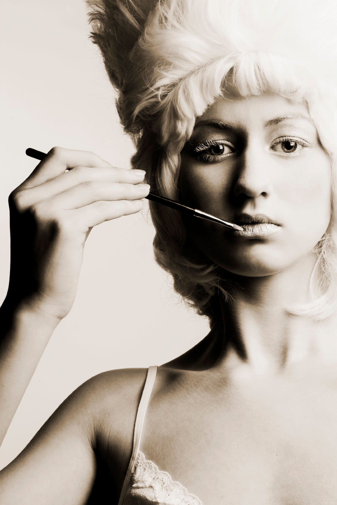 Beautiful girl with white hairdo holding a brush against her lips.[url=http://www.istockphoto.com/my_lightbox_contents.php?lightboxID=1750218]Click here for more pictures of this model![/url]